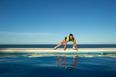 Woman doing exercises on the wall of a swimming pool with sea view in Arraial dAjuda, Bahia State, Brazil photo