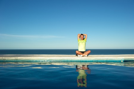 Woman doing exercises on the wall of a swimming pool with sea view in Arraial d'Ajuda, Bahia State, Brazil Stock Photo - 7219598