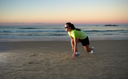 Woman doing exercises during sunset with sunglasses in Florianopolis, Santa Catarina, Brazil photo