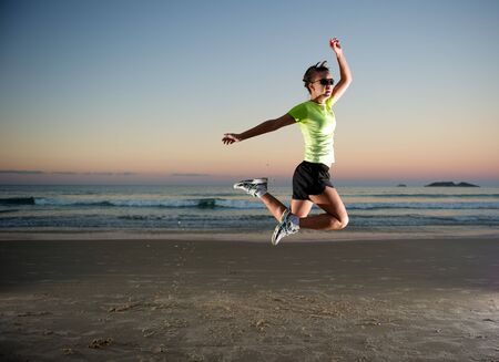 Woman doing exercises during sunset with sunglasses in Florianopolis, Santa Catarina, Brazil