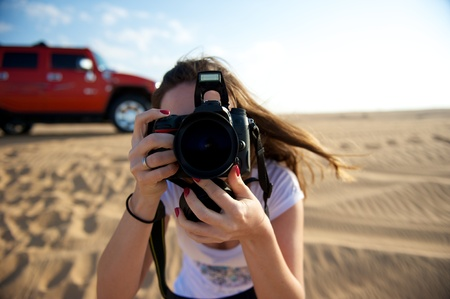 Pretty young woman taking photo in the Dubai Desert, United Arab Emirates photo