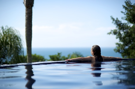 Woman relaxing in a paradise sea view swimming pool in Porto Belo, Brazil Stock Photo
