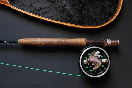 黒の背景上のギアを釣りフライします。