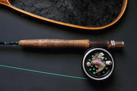 Fly fishing gear on black background photo