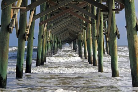 桟橋の下杭を介して波のクラッシュ 写真素材