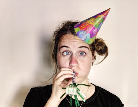 A girl with a funny face wearing a party had and blowing a streamer