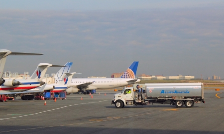 Airplanes lined up at gates with fuel truck approaching at LaGuardia Airport in Queens, NY