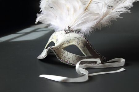 A masquerade ball mask on black with window shadow Stock Photo