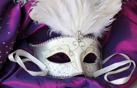 Een mardi gras gemaskerd bal masker op een jurk gemaakt van paars satijn