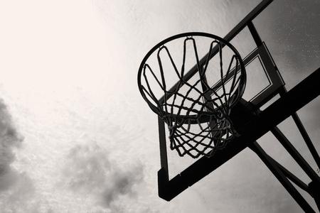 バスケット ボールのフープと白と黒の嵐の空に対してバックボード 写真素材