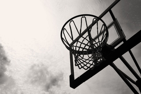 A Basketball hoop and backboard against a stormy sky in black and white