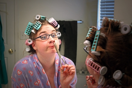 A young caucasian girl wearing a colorful robe, curlers,  and glasses makes a funny face while she trims a nose hair while looking in the mirror