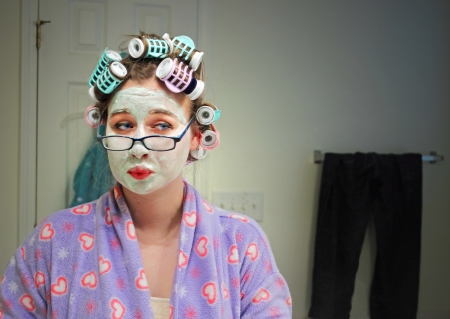 A young caucasian girl wearing a colorful robe, curlers, facial masque and glasses makes a funny face while she admires herself in a mirror