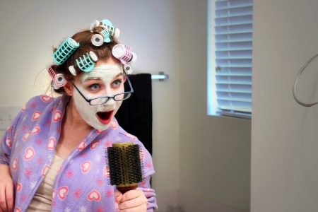 A caucasian girl wearing a colorful robe, curlers, facial mask and glasses sings into a hairbrush in front of the bathroom mirror