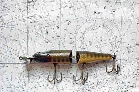 Un richiamo di pesca antico poggia su una carta nautica.
