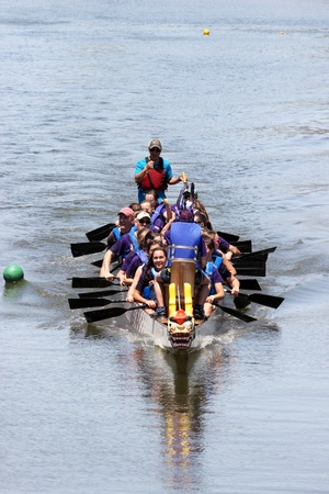 A team races at the Ground Zero Dragon Boat Races in Myrtle Beach, SC USA on Saturday April 27, 2013. Редакционное