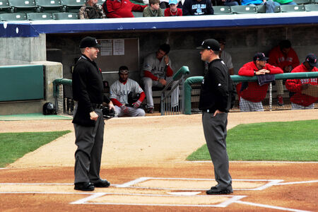 confer: Two baseball umpires confer on the field