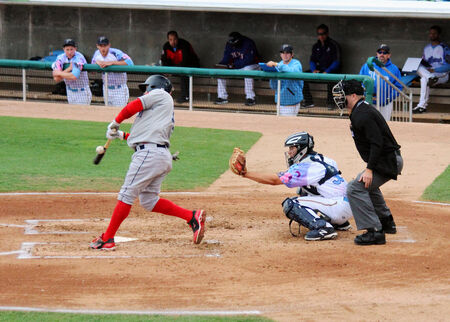 A batter swings and makes contact with the ball at homeplate  報道画像