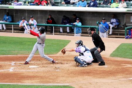dugout: A baseball batter swings at a pitch
