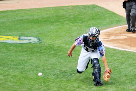 A baseball catcher chases a wild pitch