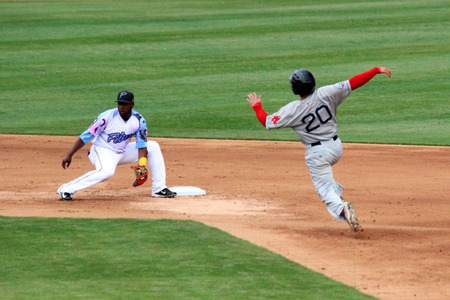 A runner begins a slide into second attempting to steal second base