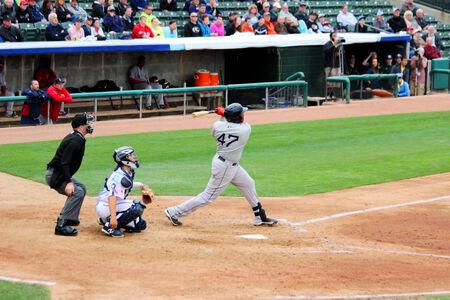 A baseball batter swings at a pitch.