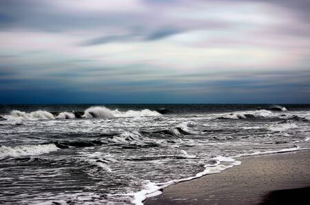 ominous: A quiet beach scene with ominous sky and waves.