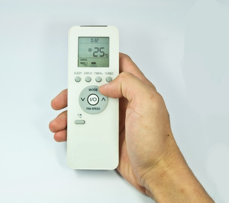 Hand is holding a remote control of air conditioner isolated Editorial