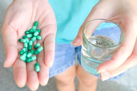 tomar medicina: Tome los medicamentos y el agua