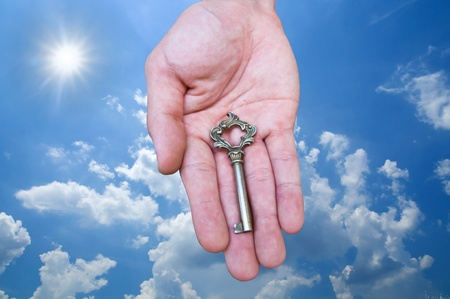 Keys in hand isolated on blue sky background photo