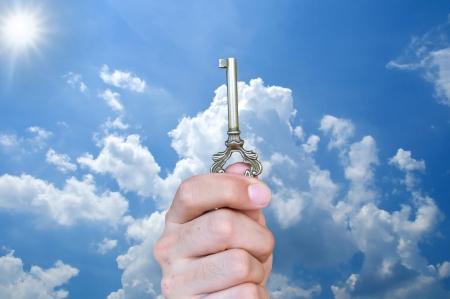 Hand holding keys on blue sky background