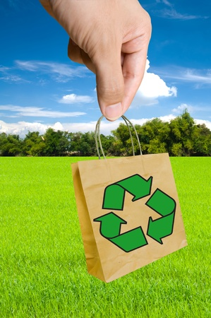 hand pick Shopping paper bag made from recycle paper with recycle symbol Stock Photo - 13263827