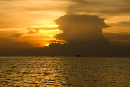 sea and sky with yellow backlit clouds coming from the sun that is shining through with light rays  Square background composition   photo