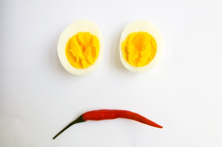 boiled egg and chilli is bored on white background