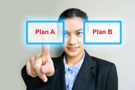 business woman hand pushing Plan A button photo