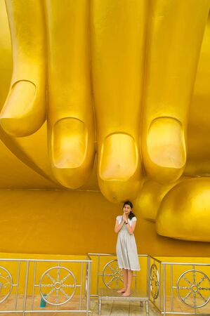 Woman pay Respect Golden Buddha statue at Wat Muang temple in Angthong, Thailand photo