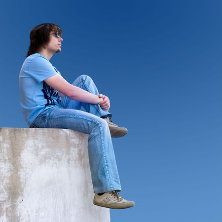 blue sky thinking: young man sitting on the wall