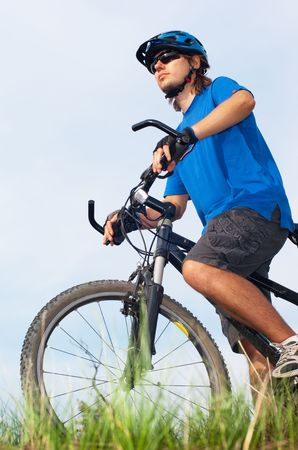 young bicyclist in a blue helmet ride bicycle on nature Stock Photo