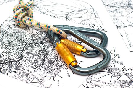 recreational climbing: two alpinism carabiners and rope on a map background