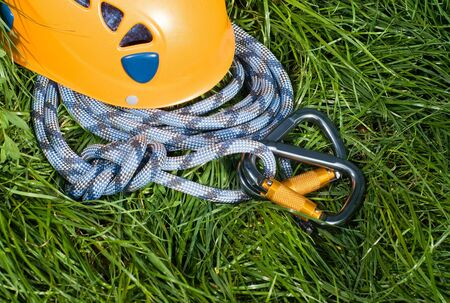 belaying: carabiners, helmet and rope on a green grass