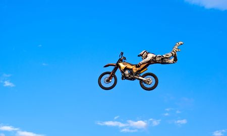 flying biker on a blue sky background photo