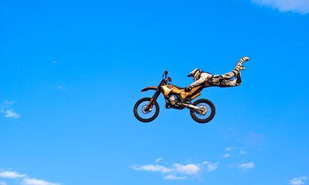 motosport: flying biker on a blue sky background
