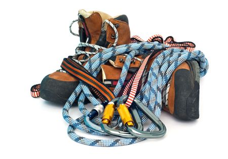 alpinism: climbing and hiking gear - three carabiners, ropes and leather brown boots