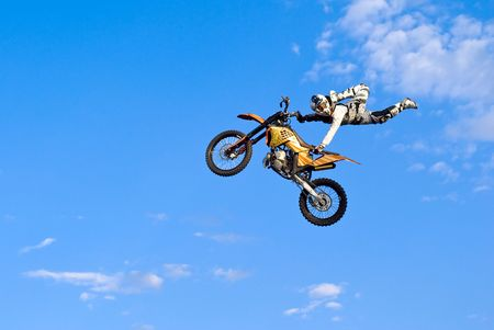 extreme: flying biker on a blue sky background