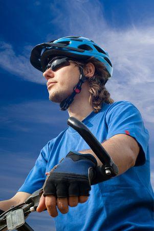 portrait of young biker in helmet on a blue sky background