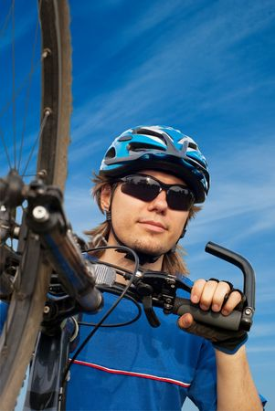 portrait of a young bicyclist in helmet with bicycle in the foreground