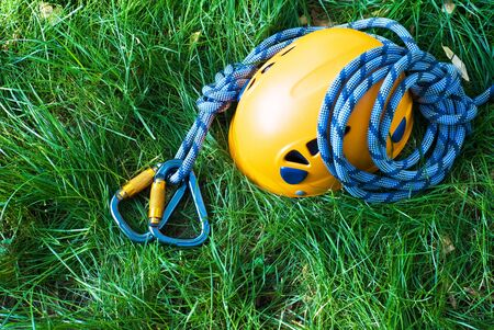 rapell: carabiners, helmet and rope on a green grass