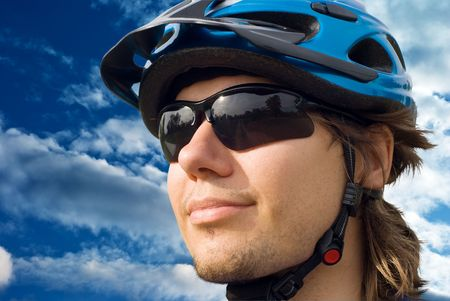 portrait of a young biker in helmet and glasses on a sky background