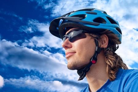 riding helmet: Retrato de un joven ciclista en casco y gafas sobre un fondo de cielo