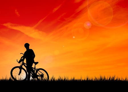 Silhouette of the biker on a sunset background Standard-Bild